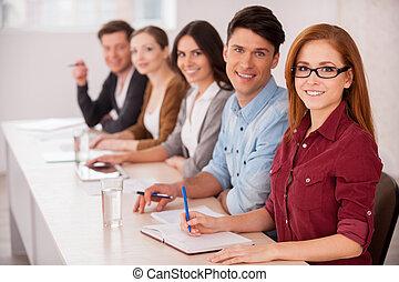 csoport, dolgozó, ülés, emberek, fiatal, együtt, fényképezőgép, együtt., asztal, mosolygós