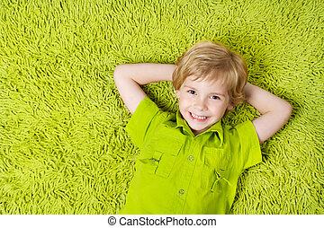 fiú, látszó, háttér., fényképezőgép, zöld, gyermek, mosolyog vidám, fekvő, szőnyeg