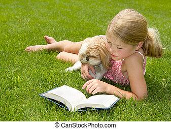 lány olvas, kutya, szabadban