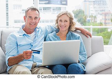 párosít, laptop, otthon, dívány, -eik, szoba, ülés, használ, mosolygós, fényképezőgép, vásárol online, boldog