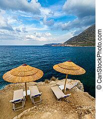 sunshades, concept., tenger, esernyők, sziklás, háttér., szünidő, szalmaszál, nyár, sunbeds, tengerpart, paradicsom, destination., idegenforgalom, sunbeds., üres, tengerpart.