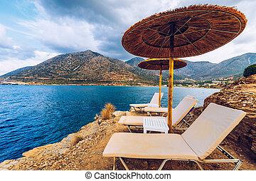 szünidő, sziklás, paradicsom, üres, idegenforgalom, sunshades, sunbeds., concept., sunbeds, tenger, tengerpart, tengerpart., szalmaszál, destination., háttér., nyár, esernyők